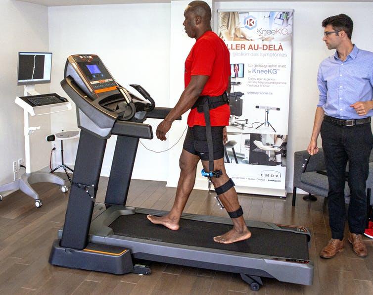Bruni Surin marche sur un tapis roulant avec un harnais attaché à la jambe